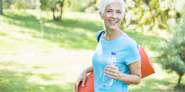 How often to exercise during chemo - elderly woman with short white hair in light blue shirt carrying water bottle and yoga mat through a park.