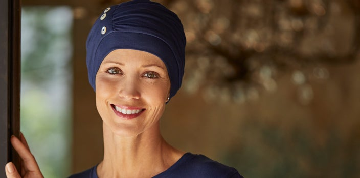 5 Reasons Why You Should Wear a Sleep Cap - Woman in navy Synergy cap standing in doorway.