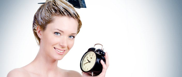 Hair dye after chemo - woman with hair dye in hair waiting with clock.