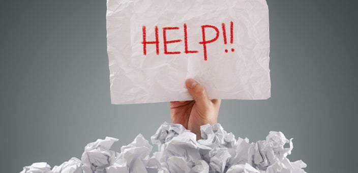 Man with Help! sign behind pile of paper: Do not be afraid to ask for help.