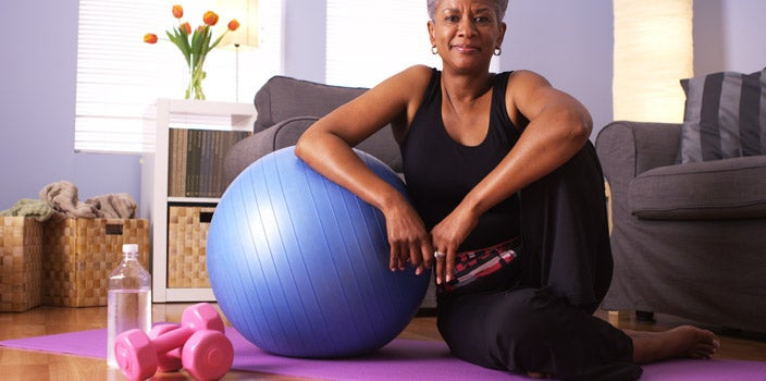 When to skip your work our - Elderly African American woman in living room with blue exercise ball, purple yoga mat, pink weights, and water bottle.