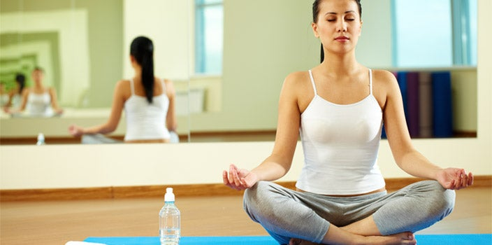 Ways to exercise during chemo - Woman in white tank top with dark brown ponytail doing yoga in studio.