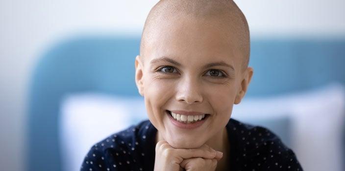 Natural bald woman smiling.
