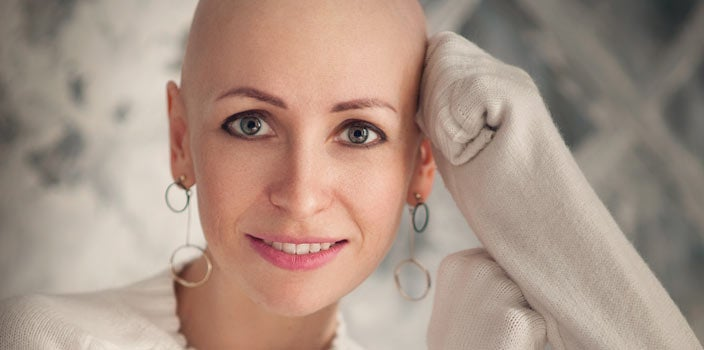 Bald woman with flattering statement earrings