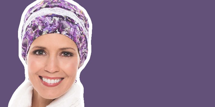 Why sleep caps are a post chemo essential - Woman in Enchanted Garden Feather Lite Sleep Cap on purple background.