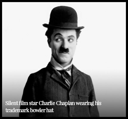 Charlie Chaplin wearing signature bowler hat.