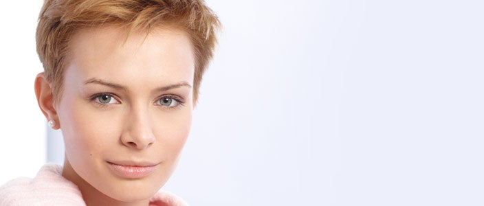 Hair dye after chemo - protect hair growth - woman in pink sweater with short blonde hair