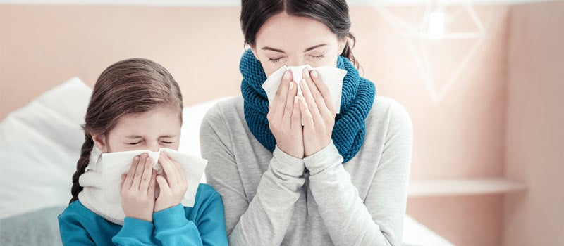 Mother and daughter coughing and sneezing into tissues
