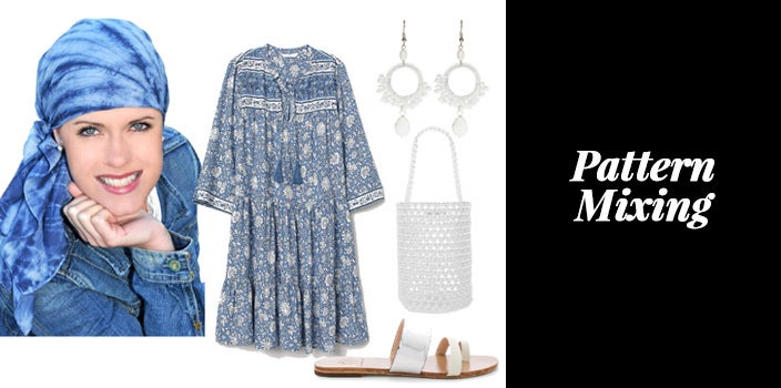 Blue tie dye headscarf with blue ditsy floral print caftan dress, white crocheted earrings, white crochet tote bag, and white slip on sandals.